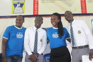 Adengo, Head of CSI and Communications Stanbic Bank (2nd right) and Brain Mulondo the quiz master of the Stanbic National Schools Championship pose for a group photo with students from Teso College Aloet